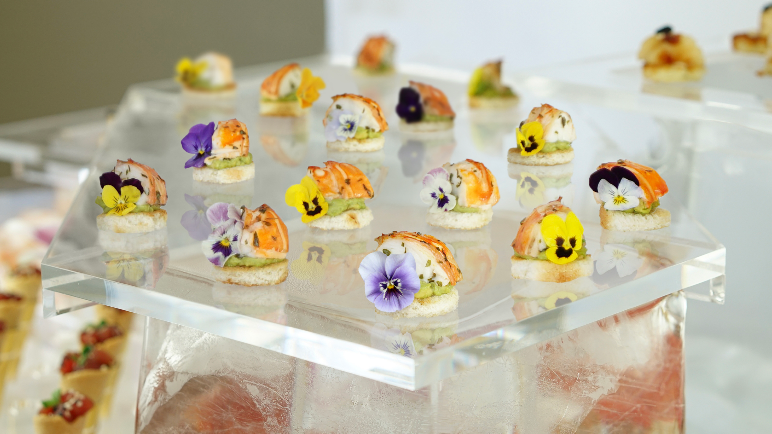 Lobster and avocado toasts with edible flowers